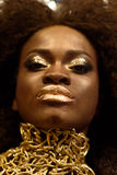Close up beauty portrait of a young female fashion model with curly hair and gold makeup.  Royalty Free Stock Image