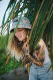 Portrait of beautiful young tattooed smiling woman standing in green leafy bush Stock Images