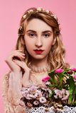 Fashion photo of young woman on pink background wearing gold diadem with flowers near her face. Close-up beauty portrait of young woman wearing gold diadem with royalty free stock photo