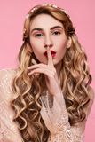 Fashion photo of young woman on pink background wearing gold diadem. Close-up beauty portrait of young woman wearing gold diadem with red lips with hands near stock photo