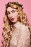 Fashion photo of young woman on pink background wearing gold diadem. Close-up beauty portrait of young woman wearing gold diadem with red lips with hands near royalty free stock image
