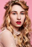 Fashion photo of young woman on pink background wearing gold diadem. Close-up beauty portrait of young woman wearing gold diadem with red lips with hands near stock images
