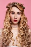 Fashion photo of young woman on pink background wearing gold diadem. Close-up beauty portrait of young woman wearing gold diadem with red lips with hands near royalty free stock images