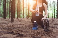 Close up of beauty sport woman resting and holding drinking water bottle and relaxing in middle of forest after tired from stock image