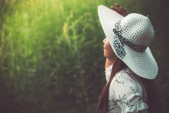 Close up of beauty woman with white dress and wing hat in the meadow background. Beauty and fashion concept. Nature and Travel royalty free stock images
