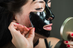 Close up of a beauty young woman taking off half of a black face mask looking at mirror.  royalty free stock photography