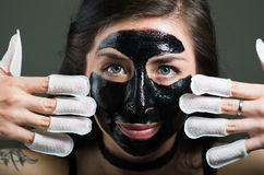 Close up of a beauty young woman using a black face mask and wearing nails protector in her nails, in a black background.  royalty free stock photography