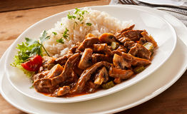 Close up of Beef goulash stroganoff. On rustic background on a white plate Stock Images