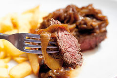 Close up of beef steak with fried onions and french fries Stock Photos