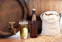 Close up of beer barrel, glass, bottle and malt Stock Images