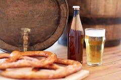 Close up of beer barrel, glass, pretzel and bottle Stock Image