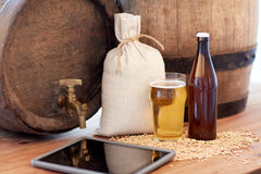Close up of beer barrel, tablet pc and malt Royalty Free Stock Image
