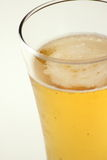 Close up of beer glass with bubbles and foam  Stock Photos