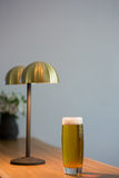 Close up of beer glass by lamp in restaurant Royalty Free Stock Photography