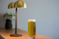 Close up of beer glass by lighting equipment in restaurant. Close up of beer glass by lighting equipment on table in restaurant Royalty Free Stock Images