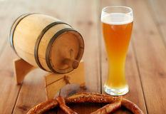 Close up of beer glass, pretzel and wooden barrel Stock Photos