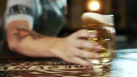 Close up of beer mug is being delivered to the client in stylish bar. Male barmen is turning the glass aroung on counter and moving it by his hand. Yellow stock footage