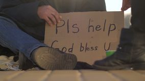 Close-up beggar male`s legs and cardboard sign. Close-up of beggar male`s legs and hands holding cardboard sign asking for help. Homeless man sitting on street stock video