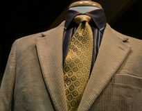 Beige Corduroy Jacket With Black Striped Shirt and Yellow Tie. Close-up of a beige corduroy jacket with black & orange striped shirt and patterned yellow tie on stock photo