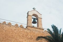 Close up of a bell over the wall of medieval moorish fortress Al. Cazaba in Almeria and cloudy sky on the background, Andalusia, Spain Stock Image