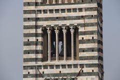 Close up of Bell tower of Duomo di Siena. The view of Romanesque stylistic patterns on Campanile. Tuscany, Italy. royalty free stock images