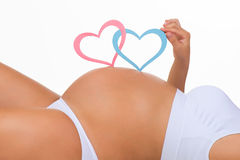 Close-up belly of pregnant woman. Gender: boy, girl or twins?. Two Hearts royalty free stock photo