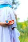 Close-up of the belly of a pregnant woman  holding boy cubes out Royalty Free Stock Image