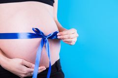 Close-up belly of pregnant woman with satin ribbon tied around it in the form of bow as gift on blue background. It`s a Boy. Baby Shower concept with copy stock image