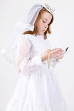 Young girl's First Communion. A close-up, from below, of a young girl smiling in her First Communion Dress and Veil, reading a bible while holding her rosary Stock Photography