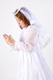 Young girl's First Communion. A close-up, from below, of a young girl smiling in her First Communion Dress and Veil, reading a bible while holding her rosary Royalty Free Stock Photo