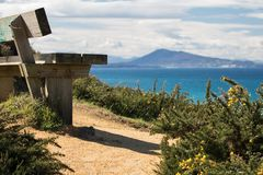 Close up on bench on coastal footpath cliff, relaxation concept, admiring scenic aerial view on atlantic coastline, bidart, france Stock Photo