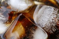Close-up beverage cola and cubes ice refreshing cool in glass, black cola soda in glass with ice cubes for refreshments feel. The close-up beverage cola and stock images