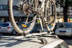 Close-up bicycle on car roof rack railing at outdoor parking. Vehicle with mounted bike on rooftop. Active sport touristic trip co stock photo
