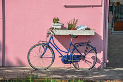 Close-up of bicycle leaning against colorful wall on a sunny day in Burano. royalty free stock photography