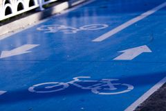 Close-up of a bicycle route sign in two directions with blue ground cover material, arrows and icons stock image