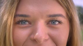 Close-up big blue eyes of caucasian woman who is looking straight and smiling outside.  stock video footage