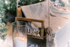Close up of big candles in glass vases near swing in a snow-cove Stock Images