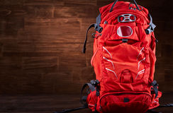 Close-up of the big hiking orange backpack against wooden background. Royalty Free Stock Photos