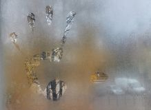 Close-up of the big male left hand print on the window. Foggy autumn morning background Stock Photography