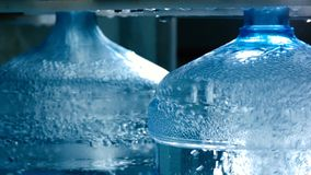 Close up big plastic containers with clean water. Bubbles in transparent liquid. Mineral water manufacturing. Water bottling factory royalty free stock photos