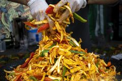 Big plate of food being stirred with hands covered by latex gloves on street market. royalty free stock images