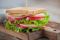 Close-up big sandwich with ham, cheese, tomatoes, salad and white sauce on toasted bread on a rustic wooden table Stock Photos