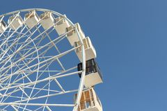Close-up big white modern ferris wheel against clear blue sky on background in Kiev city center. One black gondola among other. stock image