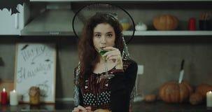 Close-up bij Halloween-partij mooi Aziatisch die meisje in een heks wordt gemaskeerd die een groene cocktail van het glas, Hallow stock video