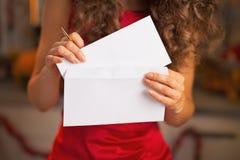 Close-up bij het womanputting van Kerstmisbrief in envelop Stock Afbeeldingen