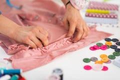 Close-up bij naaister het werken met kledingstuk stock foto's