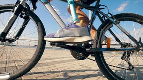 Close up of bike pedals getting spinned by a man with a bionic leg. 4K stock footage