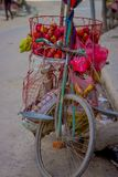 Close up of a bike with some apples fruits inside of a metallic basket in the street in historic center of city, in Royalty Free Stock Image