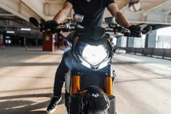Close up of biker riding motorcycle at parking. Urban background. Front view royalty free stock image