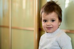 Close-up binnenportret van een babyjongen met ongehoorzaam haar De diverse emoties van een kind stock foto